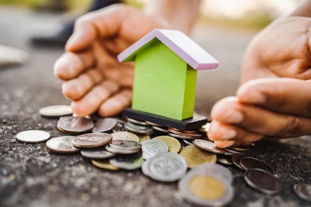 手はお金とミニハウスを保護します。節約コンセプト