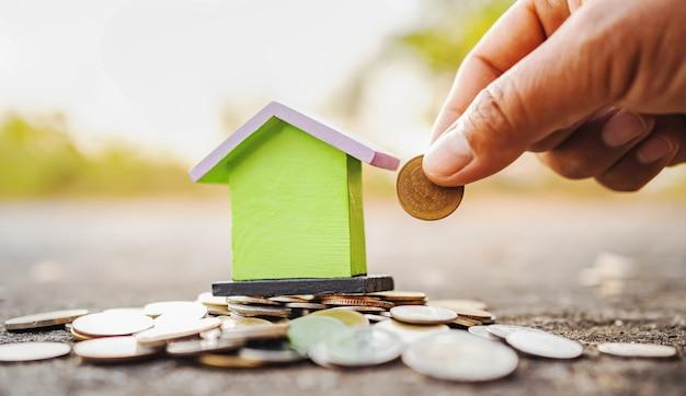 Рука экономит деньги с мини-домом и стопкой монет