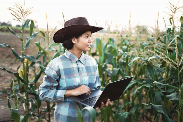 立っている若い女性は、農場でトウモロコシをチェックするラップトップを使用します。テクノロジー農業