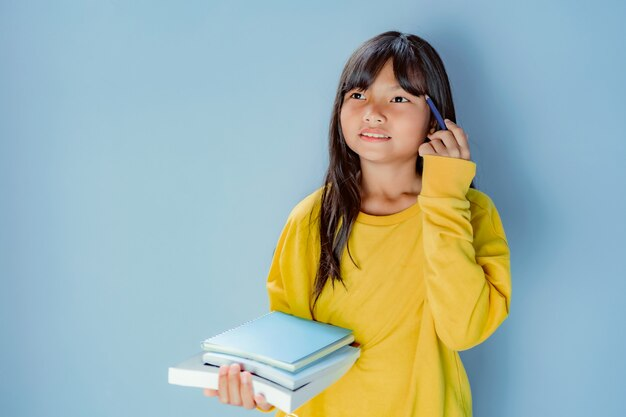 本の山を保持している女子学生