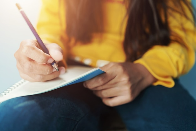鉛筆でノートに書く子供たち