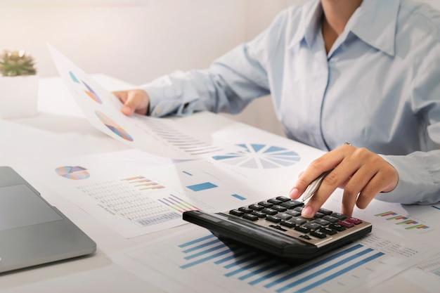 Коммерсантка работая на столе используя калькулятор и компьтер-книжку анализируя учет финансов в офисе