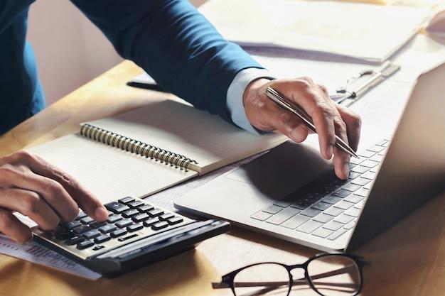 電卓とコンピューターを使用してオフィスの机で働くビジネスマン。コンセプト会計ファイナンス