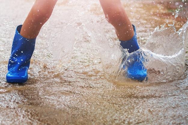 雨の日にレインブーツを着て水たまりに飛び込む子供たち