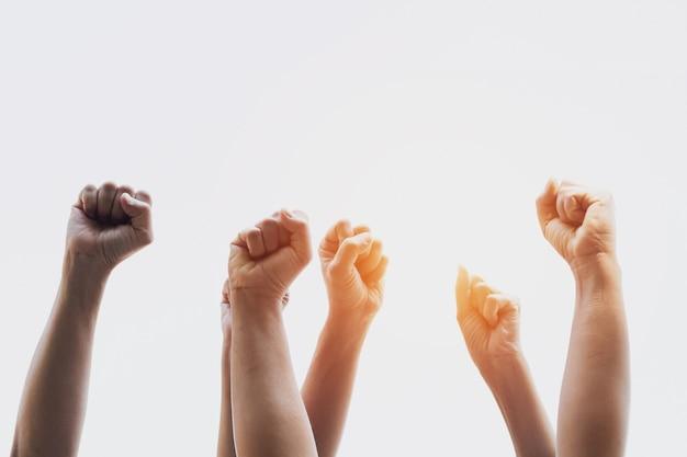 Группа людей кулаками, поднятыми с солнечным светом