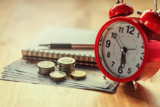 銀行と金融概念のための赤い目覚し時計でスタックとグラフをコイン