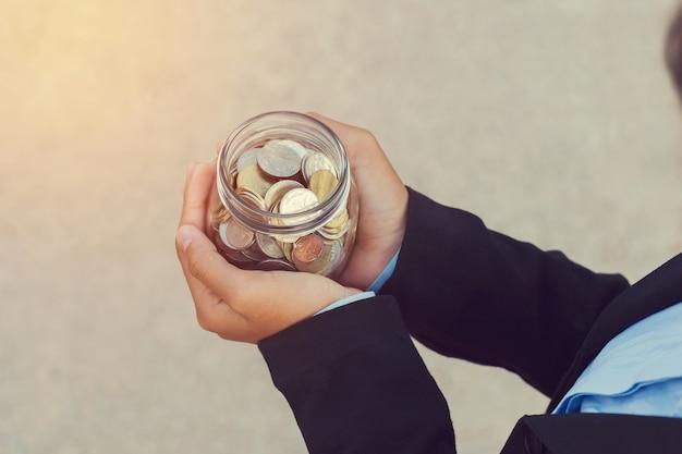 Бизнес рука монеты в стекле для экономии денег концепция финансирования