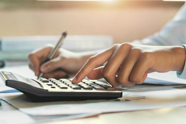 計算機、財務会計コンセプトを使用して机のオフィスで働く実業家