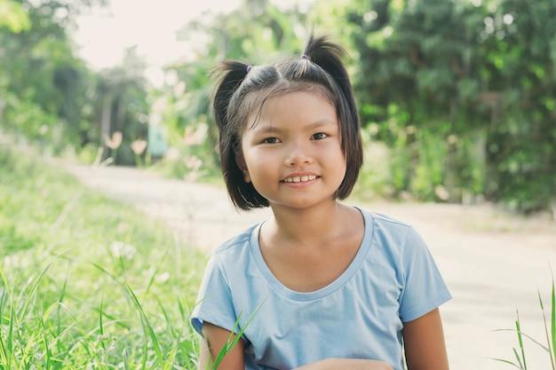 Портрет маленькая девочка, улыбаясь в парке