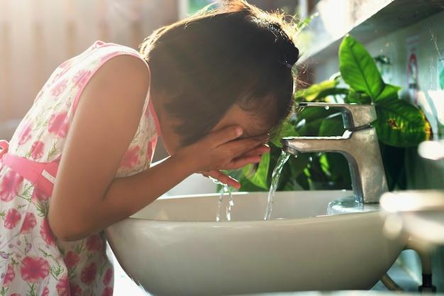 子供たちは洗面器で顔を洗う