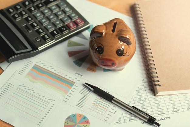 会計と財務の概念、オフィスの机の上にペン計算機と貯金箱