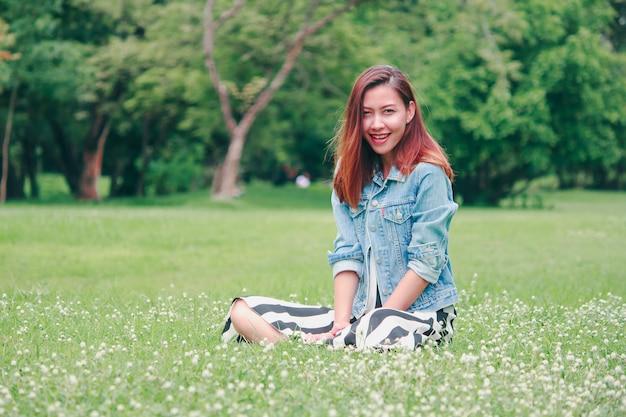 芝生に座っている長い髪の女性
