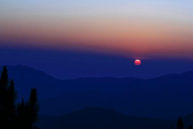 頂上に沈む夕日のオレンジ色の光。