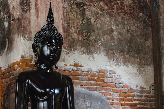 タイの寺院の古い壁と黒い仏像