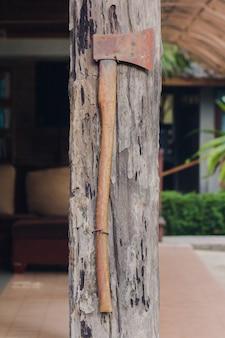 古い鉄の斧は木造住宅のポールに取り付けられています
