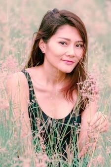 草原の美しい雰囲気の中で座っている女性。
