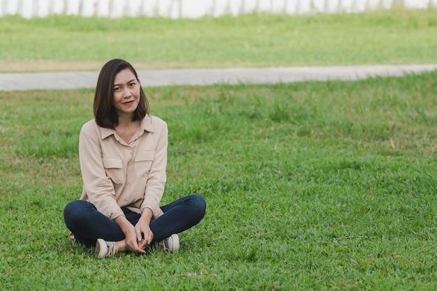 芝生の上に座っている茶色のシャツを着ている女性