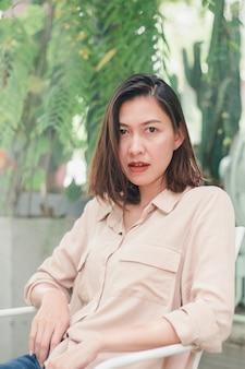 白い椅子に座っている茶色のシャツを着ている女性
