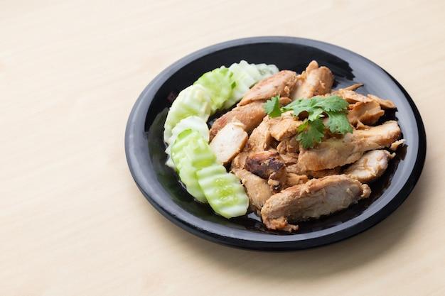 木製テーブルの上の黒い皿にキュウリと鶏の胸肉のグリルを部分的にスライスしました。