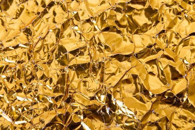Скомканная золотом предпосылка текстуры бумаги фольги.