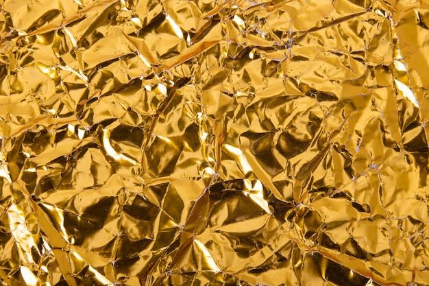 ゴールドのしわくちゃの箔紙のテクスチャ。