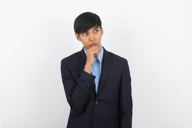 Молодой красивый азиатский бизнесмен думая идея пока смотрящ вверх изолированный