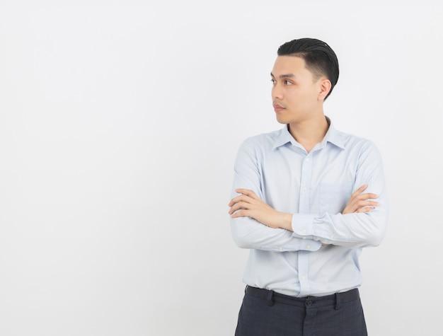Молодой красивый азиатский человек думая идея пока смотрящ вверх с пересеченными оружиями
