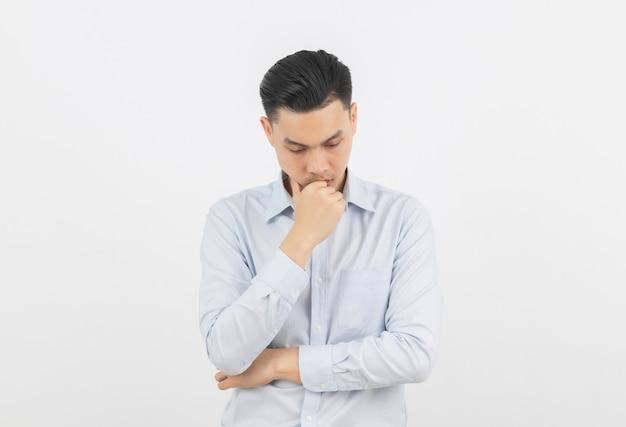 Молодой азиатский бизнесмен несчастный и разочарованный что-то. негативное выражение лица