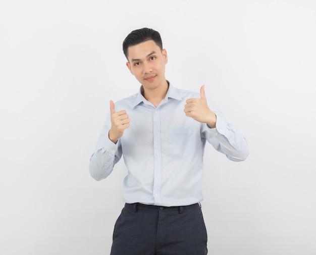 Молодой красивый азиатский бизнесмен усмехаясь и показывая большие пальцы руки вверх