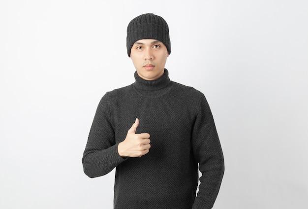 灰色のセーターとビーニーを着て親指を現してカメラを見ている若いハンサムなアジア人