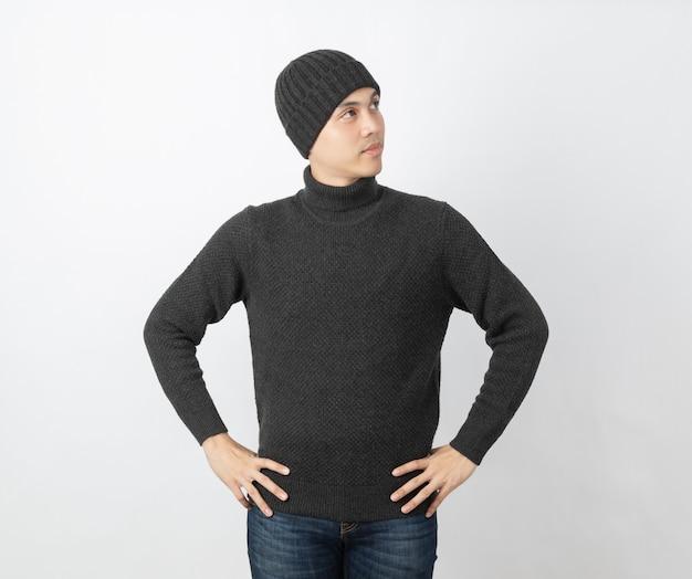 見上げながらアイデアを考えて灰色のセーターとビーニーを着ている若いハンサムなアジア人