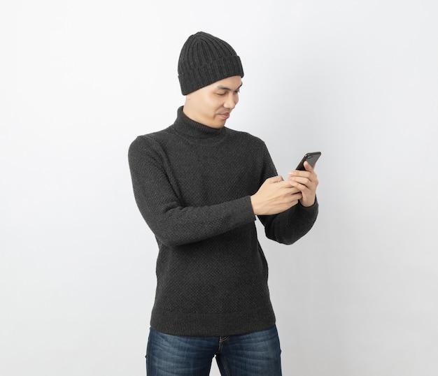 笑顔でスマートフォンをプレイしながら灰色のセーターとビーニーを着ている若いハンサムなアジア人