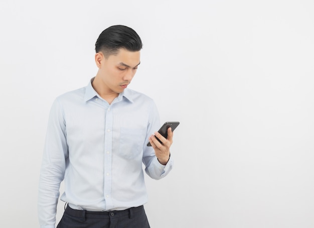スマートフォンを再生し、考えて若いハンサムなアジアビジネス男