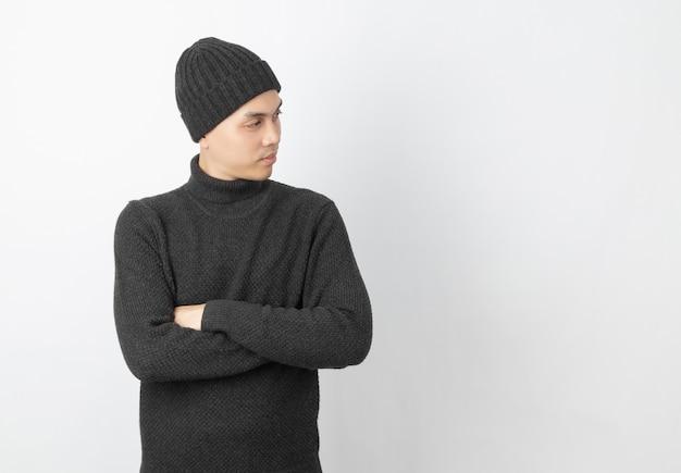 Молодой красивый азиатский человек нося серые свитер и круглую шапочку пока оружия пересекли и смотря вверх с счастливым лицом на белизне