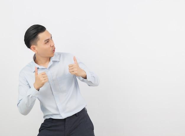 Молодой красивый азиатский бизнесмен усмехаясь и показывая большие пальцы руки вверх изолированный на белизне