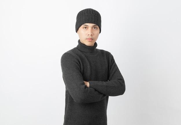 Молодой красивый азиатский человек нося серые свитер и круглую шапочку пока оружия пересекли и смотрящ к камере с счастливым лицом на белизне
