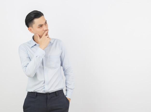 Молодой красивый азиатский бизнесмен думая идея пока смотрящ вверх изолированный на белизне