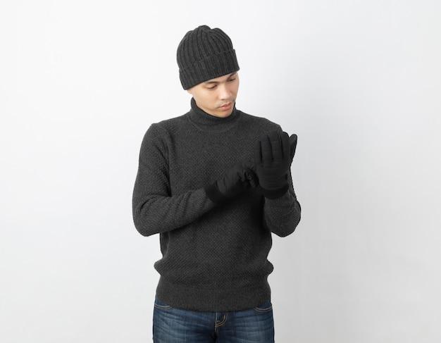 Молодой красивый азиатский человек, одетый в серый свитер, перчатки и шапочки, глядя на ее теплые перчатки на белом
