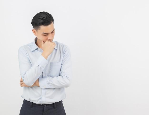 Молодой азиатский бизнесмен несчастный и разочарованный что-то. отрицательное выражение лица, изолированные на белой стене