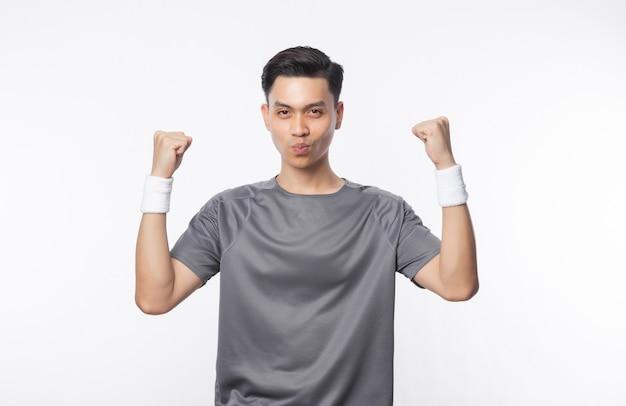 白い壁に分離された幸せそうな顔で彼のこぶしを示すスポーツ服装の若いアジア人