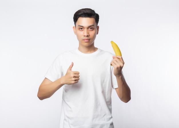 Молодой азиатский человек в белой футболке держа банан и показывая большие пальцы руки вверх изолированный на белой стене
