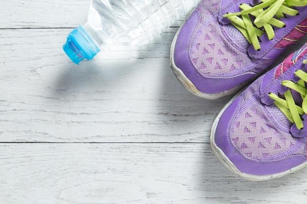 白い木製の背景にスポーツフラットレッド紫色の靴と水のボトル。