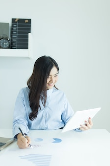 Молодая азиатская бизнес-леди используя таблетку для работы на столе в офисе с документами и компьтер-книжкой.