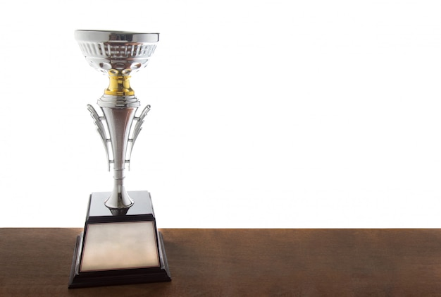 白い背景の上に隔離された木製のテーブルに銀のトロフィー。コピースパで賞を受賞