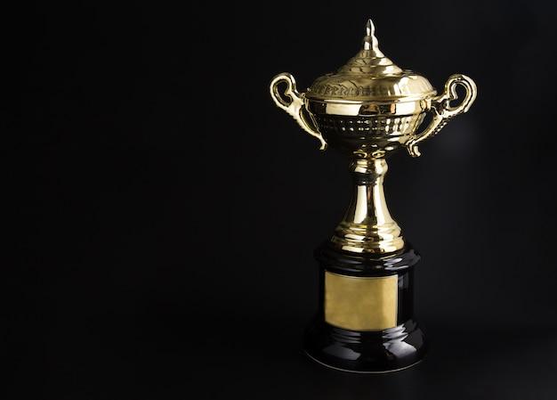 黒の背景の上にゴールデントロフィー。テキストとデザインのためのコピースペースで賞を受賞。