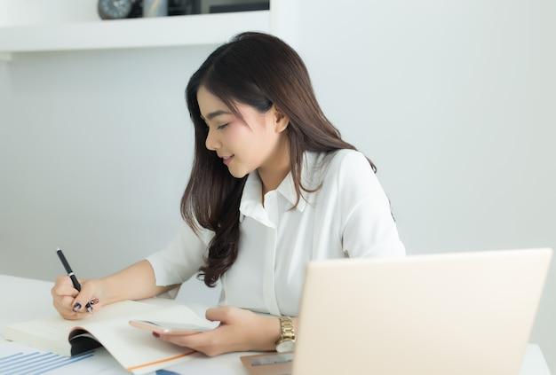 Молодая азиатская бизнес-леди усмехаясь и работая на ее рабочем месте.