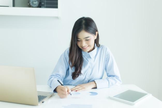 Молодая азиатская бизнес-леди работая на столе в офисе с документами и компьтер-книжкой.