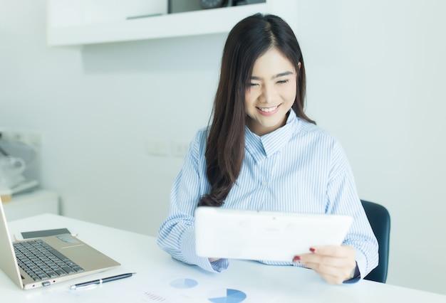 Молодая азиатская бизнес-леди используя таблетку для работы в офисе с документами и компьтер-книжкой.