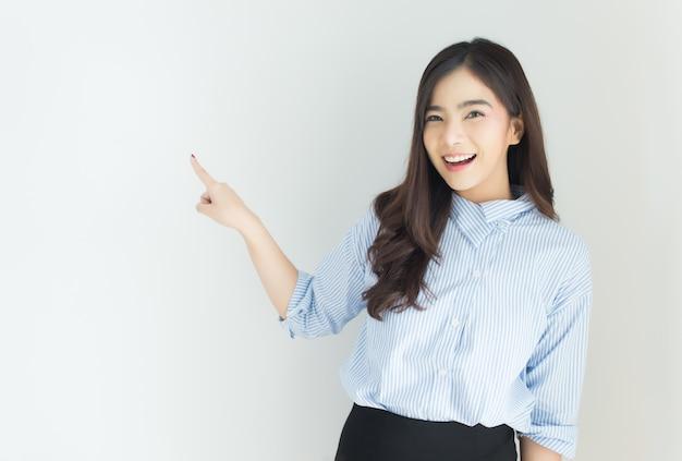 Портрет молодой азиатской бизнес-леди указывая вверх над белой предпосылкой.