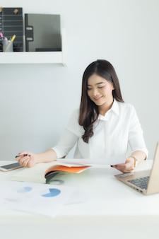 Молодая азиатская бизнес-леди думая и работая на ее рабочем месте.